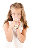 Smiling little girl drinking milk isolated on a white Stock Image