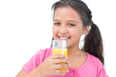 Smiling little girl drinking orange juice Royalty Free Stock Image