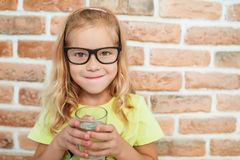 Smiling little girl drinks water Stock Images