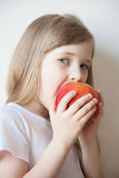 Smiling little girl eating a big red apple Royalty Free Stock Images