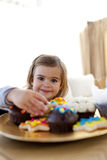 Smiling little girl eating confectionery at home Stock Photography