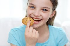Smiling little girl eating cookie or biscuit stock images