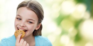 Smiling little girl eating cookie or biscuit Stock Image