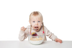 Smiling little girl eating flakes. Isolated on white background. Smiling little girl eating breakfast. Isolated on white background stock photos