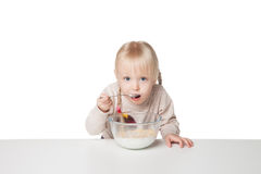 Smiling little girl eating flakes. Isolated on white background. Smiling little girl eating breakfast. Isolated on white background royalty free stock image