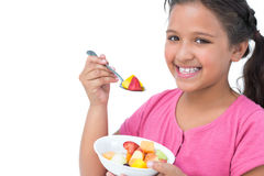 Smiling little girl eating fruit salad Royalty Free Stock Image