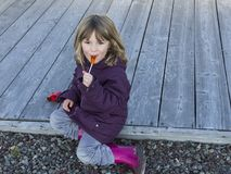 Smiling little girl eating a lollipop stock images