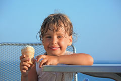 Smiling little girl eats ice-cream on resort Stock Photos