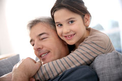 Smiling little girl embracing her father Stock Images