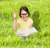 Smiling little girl in eyeglasses with book Royalty Free Stock Photography