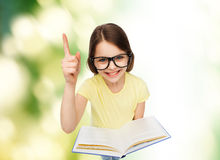 Smiling little girl in eyeglasses with book Royalty Free Stock Photo