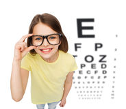 Smiling little girl in eyeglasses with eye chart. People, childhood, healthcare and vision concept - smiling little girl in black eyeglasses over white Stock Photos