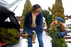 Smiling little girl and father get christmas tree out of car trunk near their house outdoors. Daughter helps dad with. New year home decorations and fir-tree on royalty free stock photography