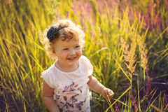 Smiling little girl on the field Royalty Free Stock Photos
