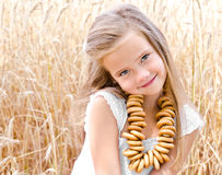 Smiling little girl on field of wheat with bagels Stock Photography