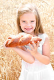 Smiling little girl on field of wheat with bread Stock Photos