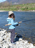 Smiling little girl fishing  on the river Stock Photos