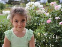 Smiling little girl and flowers Royalty Free Stock Photo
