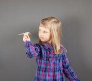 Smiling little girl flying paper plane Stock Image