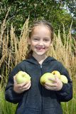 A smiling little girl without foretooth holds in her hands a lot of apples stock photography