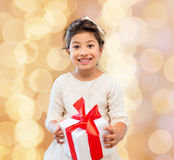 Smiling little girl with gift box. Holidays, presents, christmas, childhood and people concept - smiling little girl girl with gift box over beige lights Stock Images