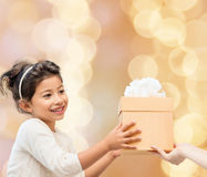 Smiling little girl with gift box. Holidays, presents, christmas, childhood and people concept - smiling little girl with gift box over beige lights background Stock Image