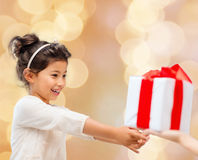 Smiling little girl with gift box. Holidays, presents, christmas, childhood and people concept - smiling little girl with gift box over beige lights background Royalty Free Stock Photo