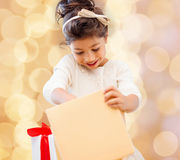 Smiling little girl with gift box. Holidays, presents, christmas, childhood and people concept - smiling little girl with gift box over beige lights background Royalty Free Stock Images