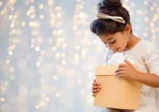 Smiling little girl with gift box over lights Royalty Free Stock Photography