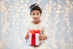 Smiling little girl with gift box over lights Stock Photos