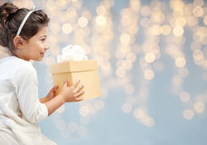Smiling little girl with gift box over lights Stock Photo