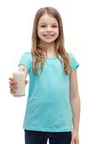 Smiling little girl giving glass of milk Stock Photos