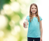 Smiling little girl giving glass of milk Stock Photo