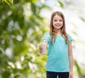 Smiling little girl giving glass of milk Stock Image