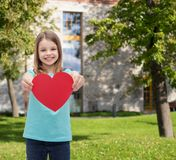 Smiling little girl giving red heart Royalty Free Stock Image
