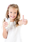 Smiling little girl with glass of milk and finger up Royalty Free Stock Photography