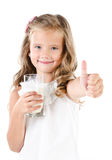 Smiling little girl with glass of milk and finger up Royalty Free Stock Photo