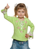 Smiling little girl in green with her thumb up Royalty Free Stock Photography