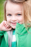 Smiling little girl in green jacket Royalty Free Stock Photo