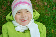Smiling little girl in green jacket Stock Photos