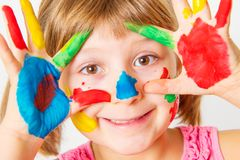 Smiling little girl with hands painted in colorful paints. A smiling little girl with hands painted in colorful paints royalty free stock images