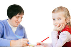 Smiling little girl and happy mature woman draws Stock Photo