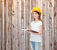 Smiling little girl in hardhat with clipboard. Childhood, construction, architecture, building and people concept - smiling little girl in protective helmet with Stock Image