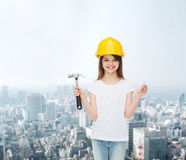 Smiling little girl in hardhat with hammer Royalty Free Stock Image
