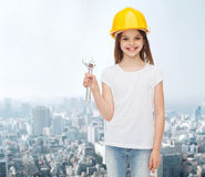 Smiling little girl in hardhat with wrench Stock Photo