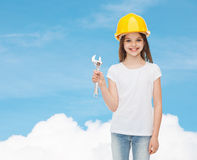 Smiling little girl in hardhat with wrench Royalty Free Stock Photography
