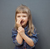Smiling little girl has a secret. Grey background Stock Images