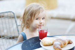 Smiling little girl having breakfast Stock Photo