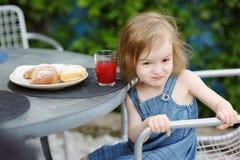 Smiling little girl having breakfast Stock Photos