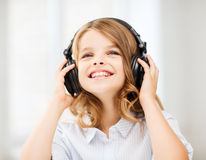Smiling little girl with headphones at home. Home, leisure, new technology and music concept - smiling little girl with headphones at home royalty free stock photos